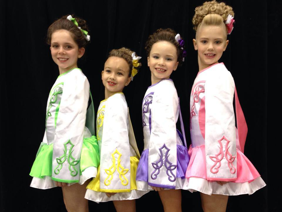 Four 8-9 year old girls in pastel Irish dance dresses.