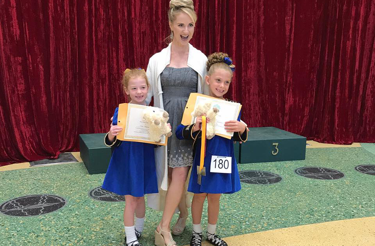 Dance teacher with two young first feis dancers in dresses, smiling.